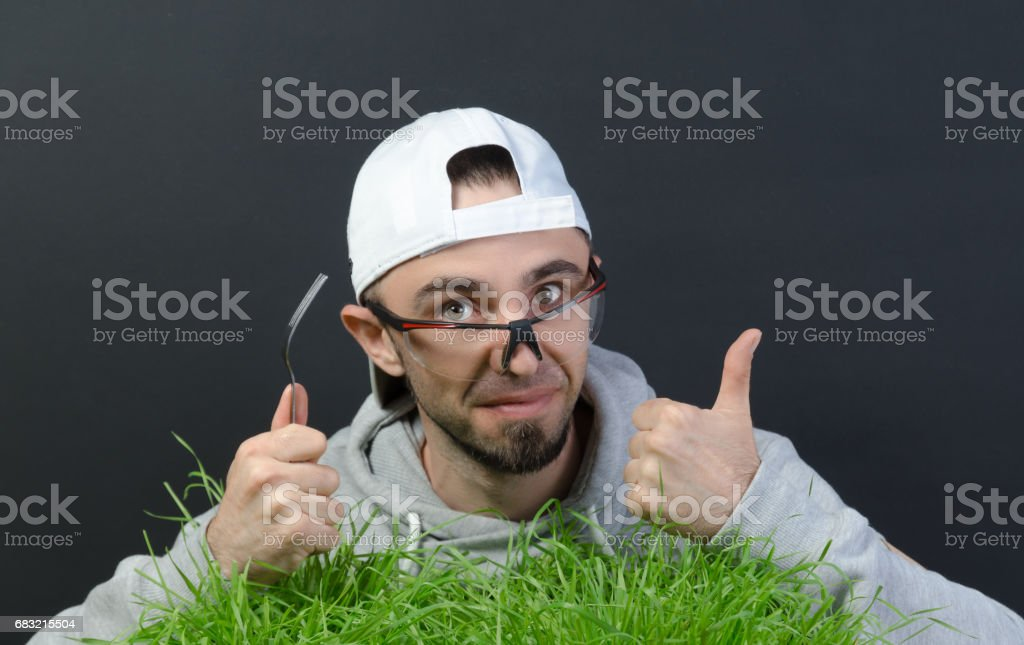 the guy eats the green grass foto de stock royalty-free