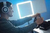 istock The guy gamer with headset playing video games on the illuminated background 1218726702