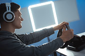 istock The guy gamer with headset playing video games on the illuminated background 1277112417