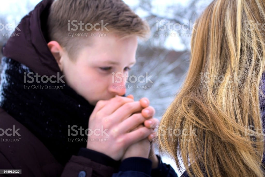 The guy gently warms his hands with the young girl, lovingly looks into her eyes, she sincerely smiles. stock photo
