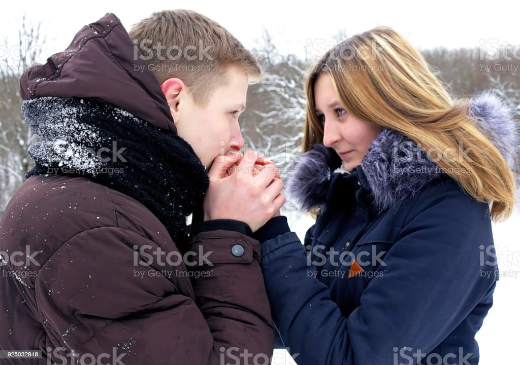 The guy gently warms his hands with the young girl, lovingly looks into her eyes, she sincerely smiles. Young couple, first love. stock photo