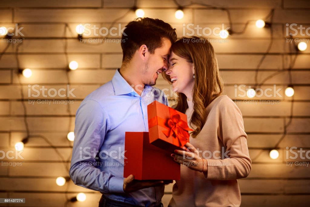 The guy gives a gift box to his girlfriend. stock photo