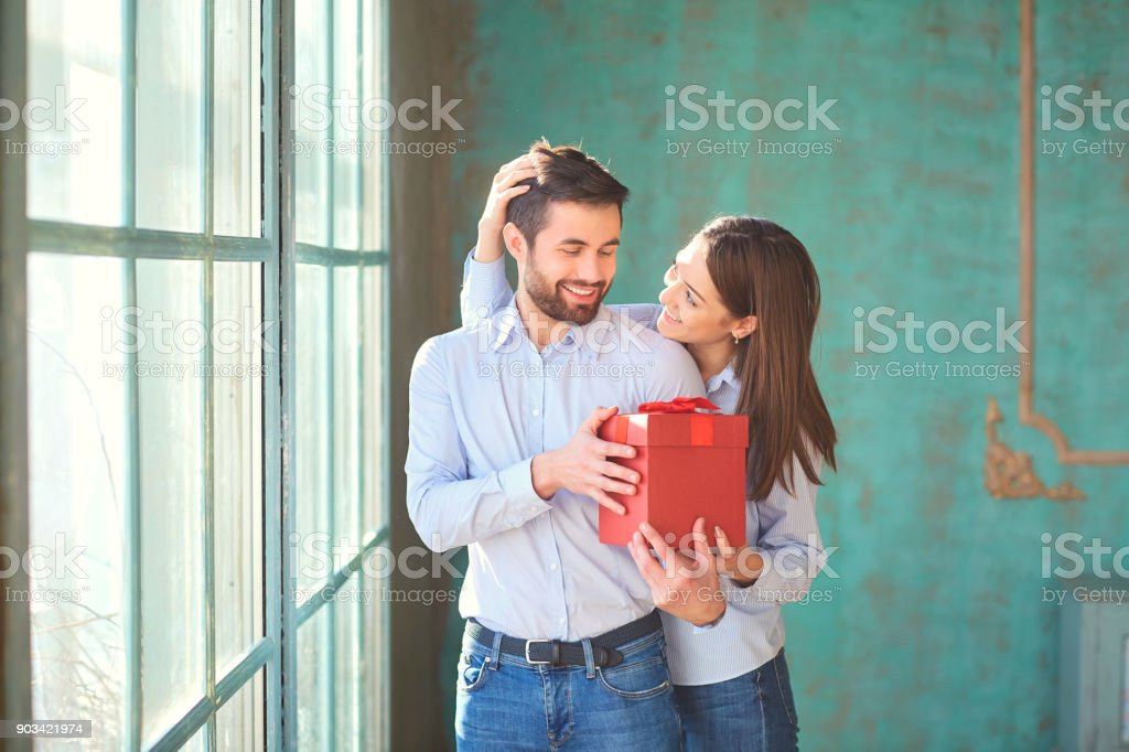 The guy gives a gift box to his girlfriend stock photo