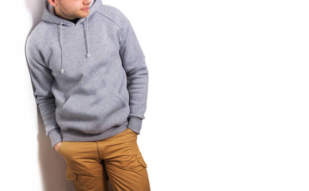 the guy in the blank grey hoodie, sweatshirt, stand, smiling on a white background, mock up, free space,  template for print,  design stock photo