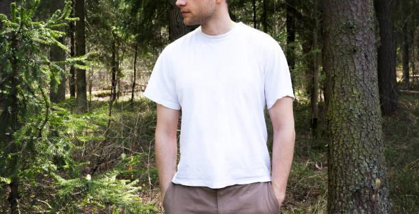 killen i tomrummet vita t-shirt, stativ i grön skog bakgrunden, håna upp bildbanksfoto