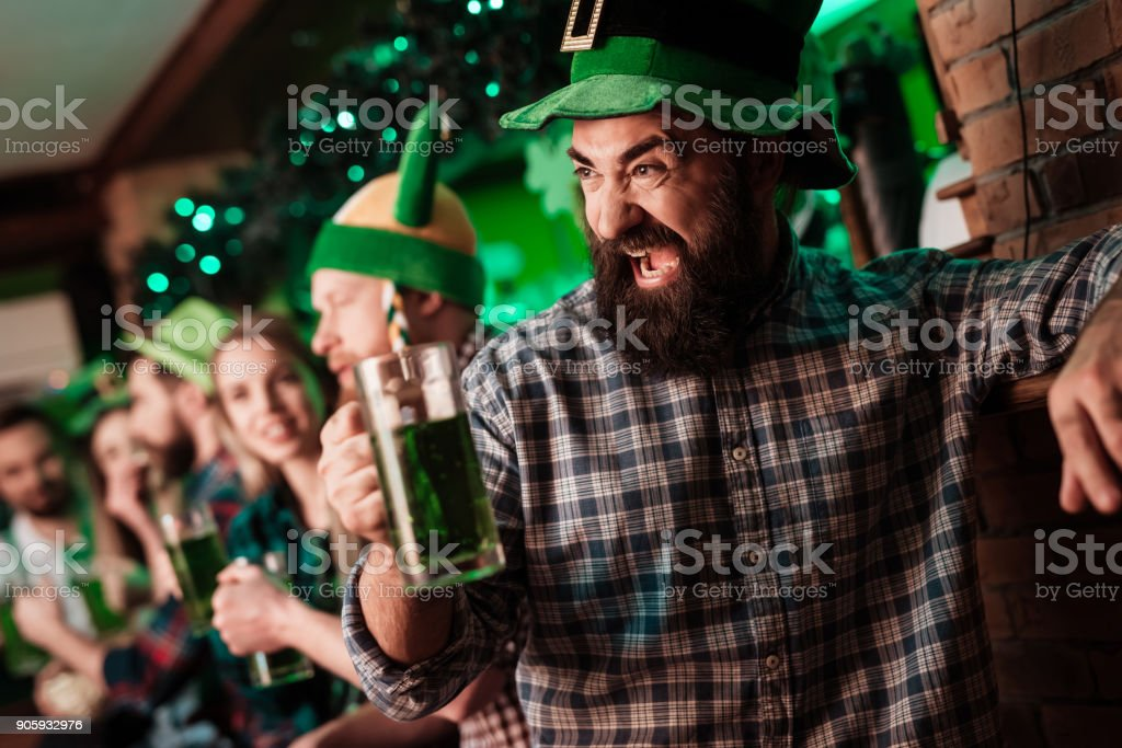 The guy in the cap of the leprechaun is drinking beer. stock photo