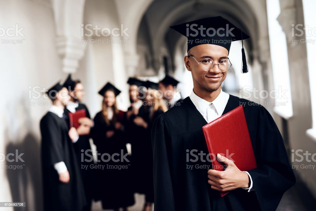 The guy in the mantle poses at the university. stock photo