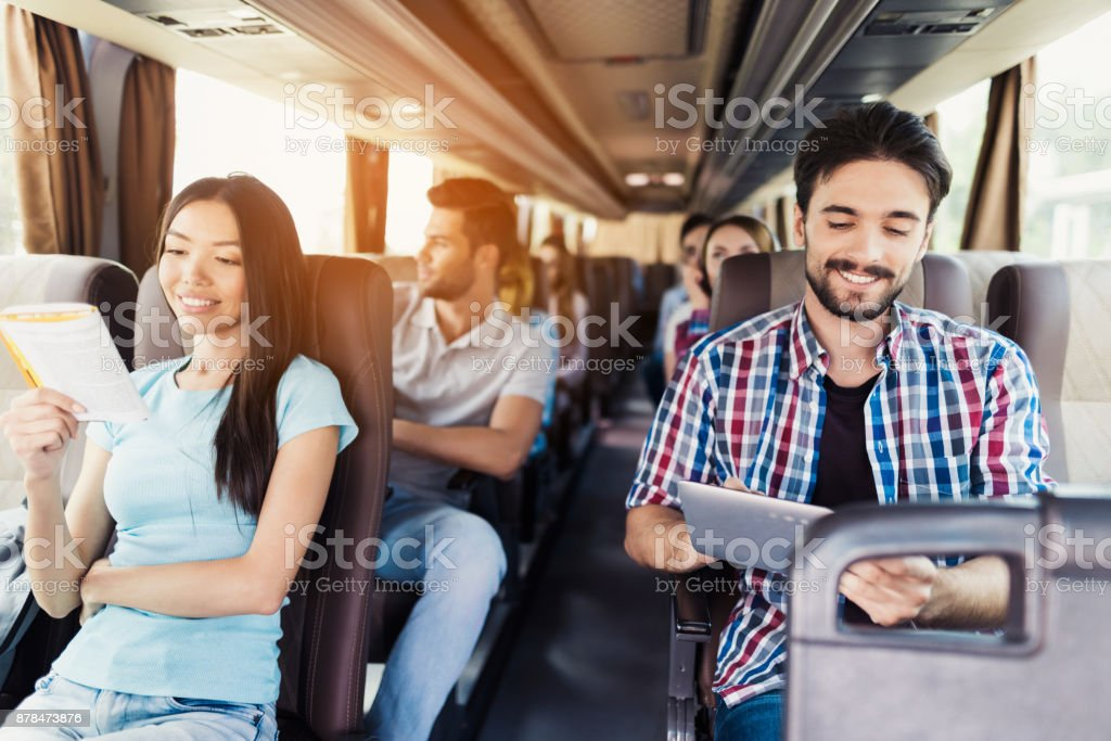 The guy in the shirt sits on the bus and looks at something on his gray tablet. He smiles. stock photo