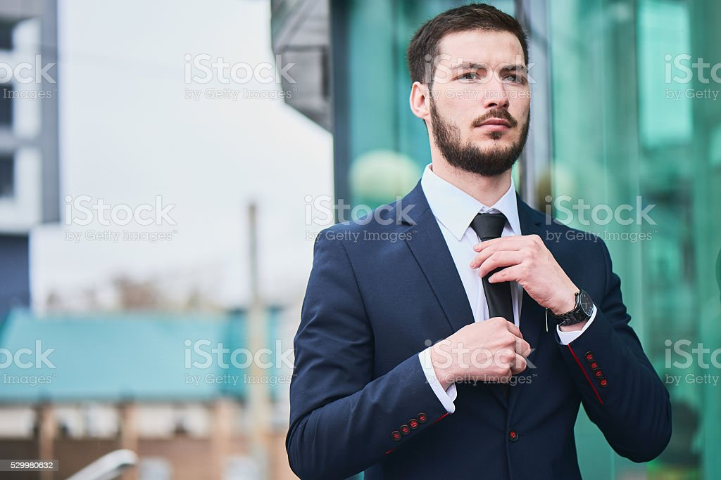 The guy in the suit straightens his tie stock photo