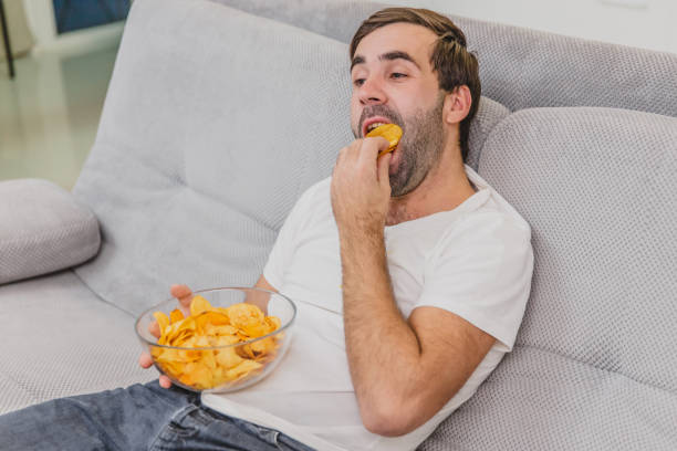the guy in the t-shirt sits on the couch, eats chips and watches the tv. while holding the remote in his hands. personality at home. - chip komputerowy zdjęcia i obrazy z banku zdjęć