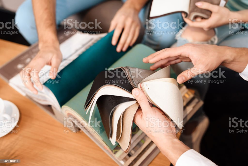 The guy is holding leather samples for the upholstery of the sofa. stock photo