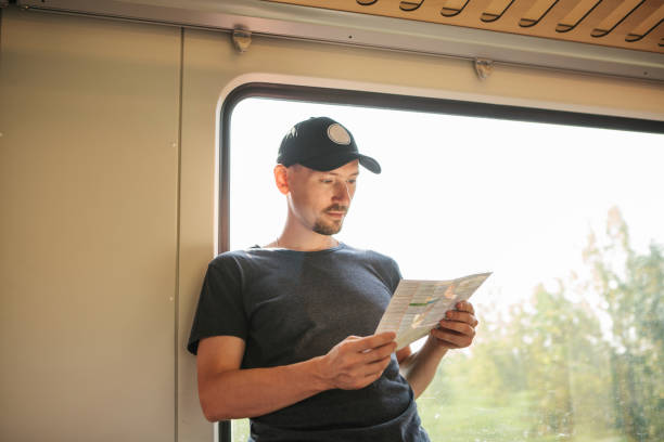 The guy is looking the map Tourist at the window in the train looks the map. electric train stock pictures, royalty-free photos & images