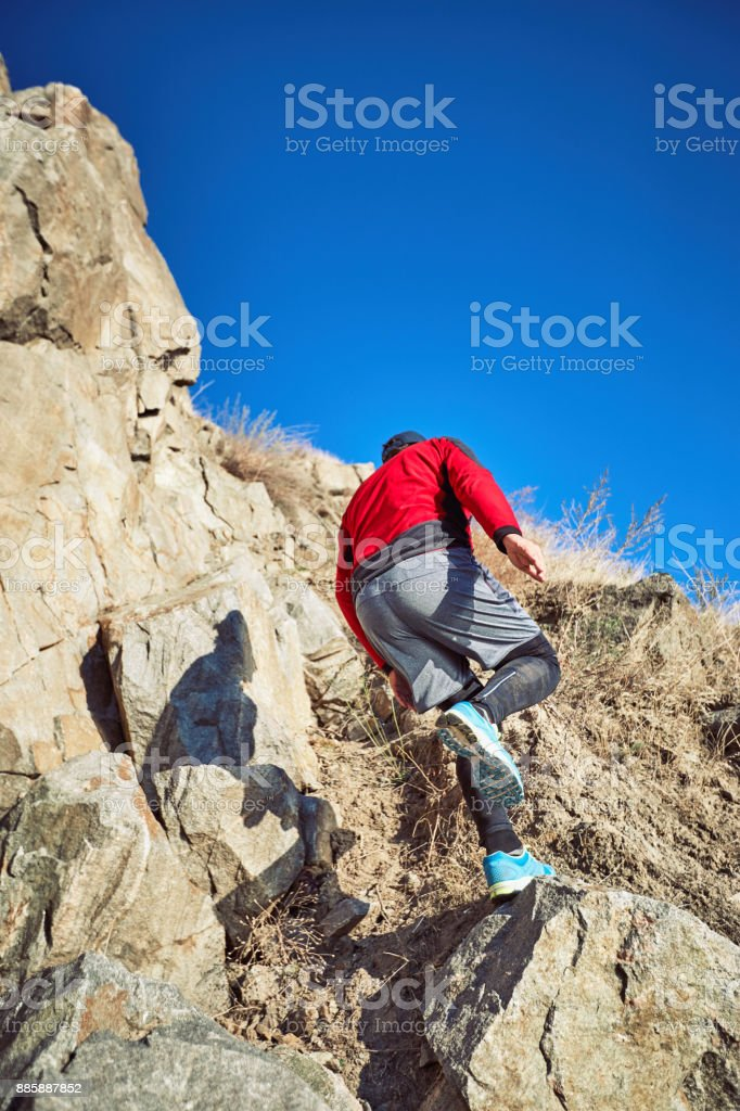 The guy is running on a difficult terrain in the mountains. stock photo