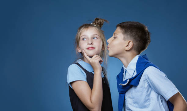 the guy kisses the girl on the cheek - kids kiss embarrassed foto e immagini stock