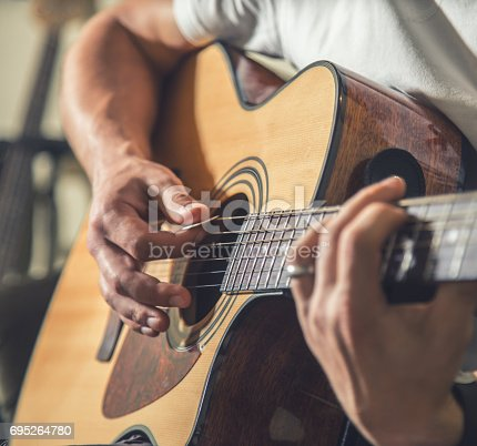 istock the guy playing the acoustic guitar 695264780