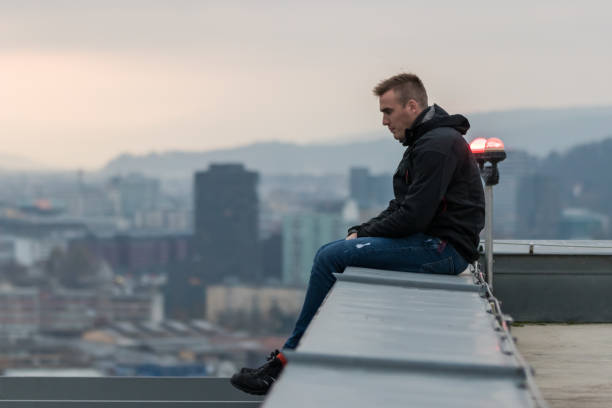 The guy sitting on the edge of the roof and looking at city with sunset The guy sitting on the edge of the roof and looking at city with sunset suicide stock pictures, royalty-free photos & images