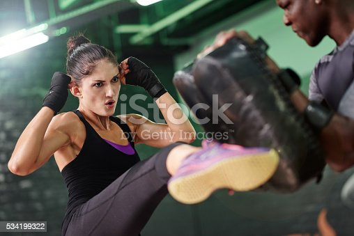 Shot of a female kick-boxer practising with her coach in a gym