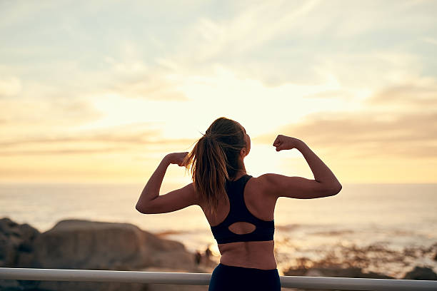 The habit of persistence is the habit of victory Shot of a young sporty woman flexing after her workout early 20th century stock pictures, royalty-free photos & images