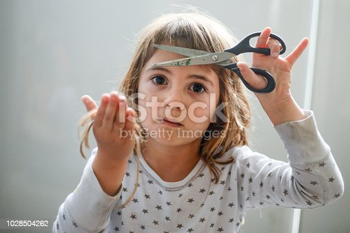 Cute little 4 year old girl holds a pair of scissors in one hand and the hair she cut from her head in the other hand.
