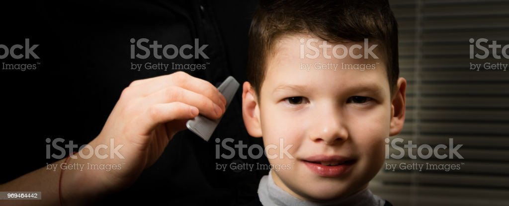 the hairdresser does a hairstyle for the boy with a smile on his face stock photo
