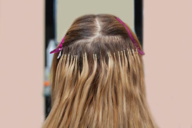 der friseur tut haarverlängerungen, ein junges mädchen, eine blondine in einem schönheitssalon. - haarverlängerungsstile stock-fotos und bilder