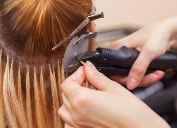 미용사 젊은 여자, 뷰티 살롱에서 금발 머리 확장을 한다. - 붙임 머리 뉴스 사진 이미지
