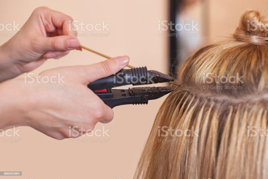 O cabeleireiro faz extensões de cabelo de uma mulher, uma loira - foto de acervo