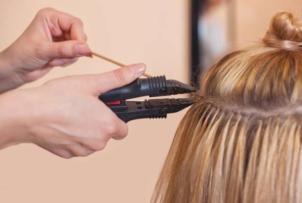 friseur tut haarverlängerung, um ein junges mädchen, eine blondine - haarverlängerungsstile stock-fotos und bilder