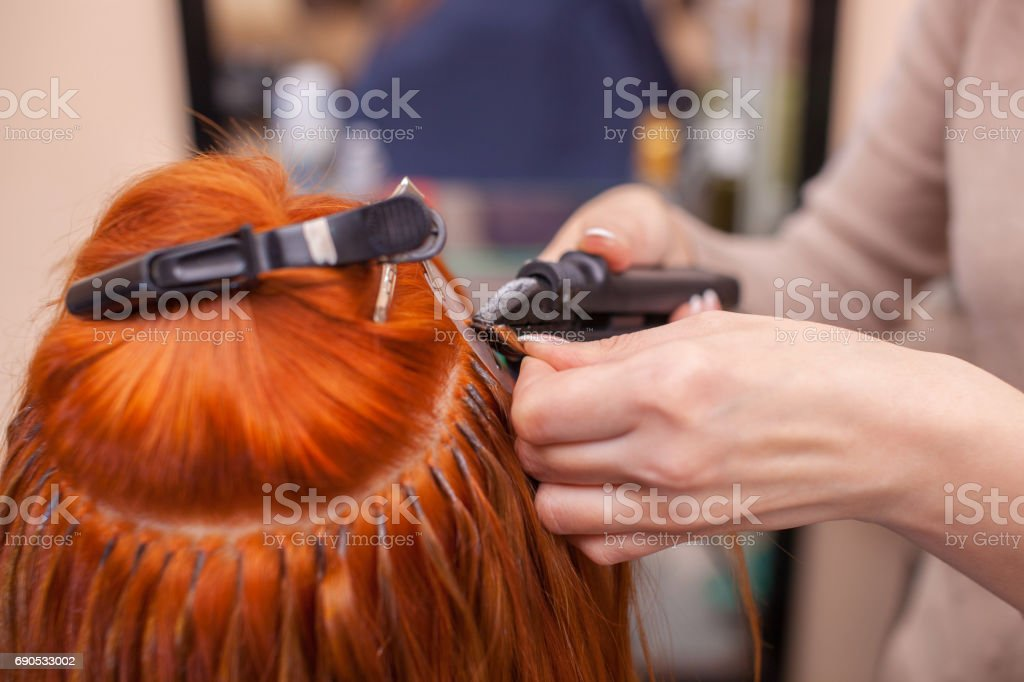 The hairdresser does hair extensions to a young, red-haired girl, in a beauty salon stock photo