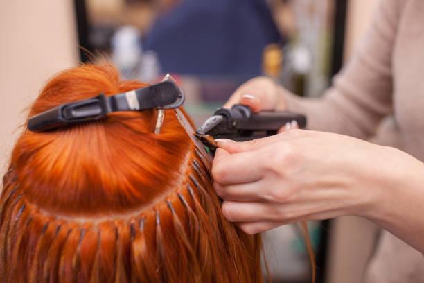 der friseur hat haarverlängerungen, ein junge, rothaarige mädchen in einem schönheitssalon - haarverlängerungsstile stock-fotos und bilder