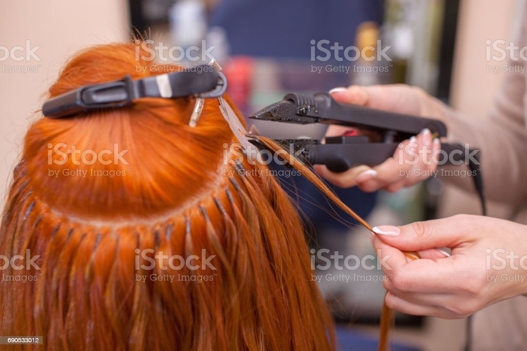 The hairdresser does hair extensions to a young redhaired girl in the hairdresser does hair extensions to a young red haired girl in a pmusecretfo Image collections