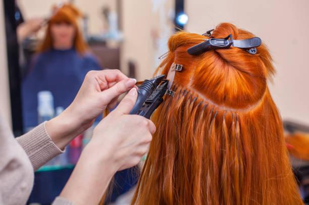 der friseur macht haarverlängerungen, ein junge, rothaarige mädchen in einem schönheitssalon. - haarverlängerungsstile stock-fotos und bilder