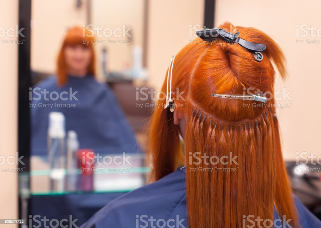 The hairdresser does hair extensions to a young, red-haired girl, in a beauty salon. stock photo