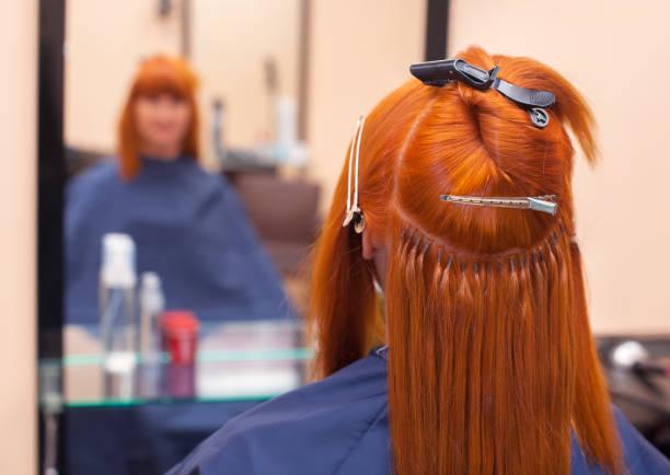 Der Friseur macht Haarverlängerungen, ein Junge, rothaarige Mädchen in einem Schönheitssalon. – Foto