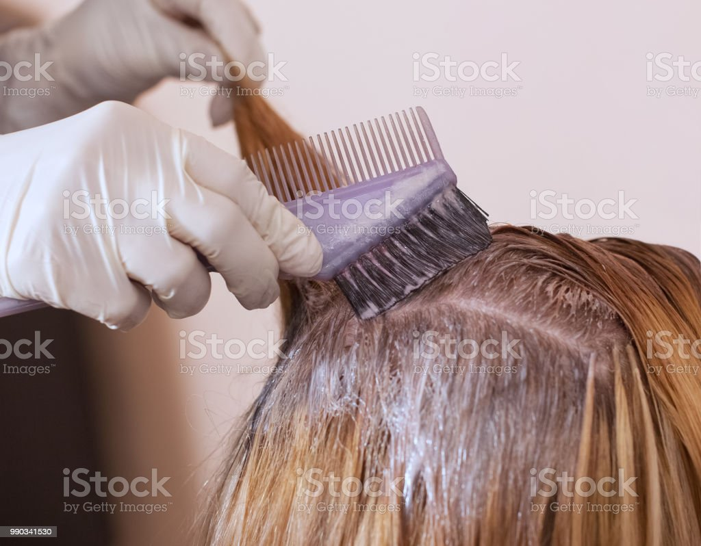 The hairdresser paints the woman's hair in white, apply the paint to her hair stock photo