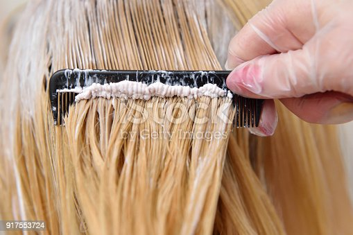 istock The hairdresser smears the paint on his hair with a comb 917553724