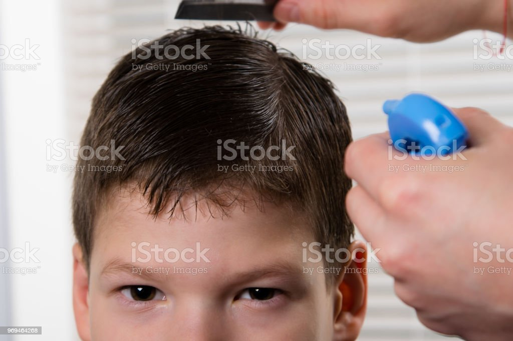 the hairdresser to the boy moisturizes his hair and does his hair stock photo