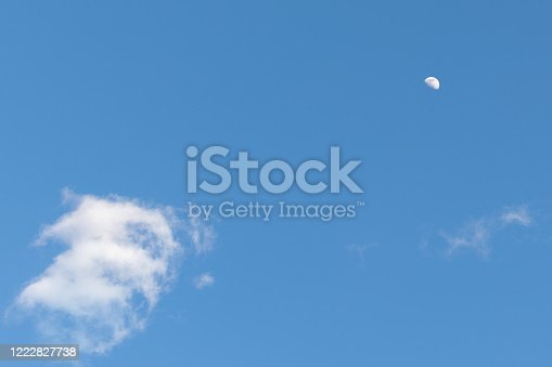 A bright blue sky contrasted by puffy white clouds and the bright moon.