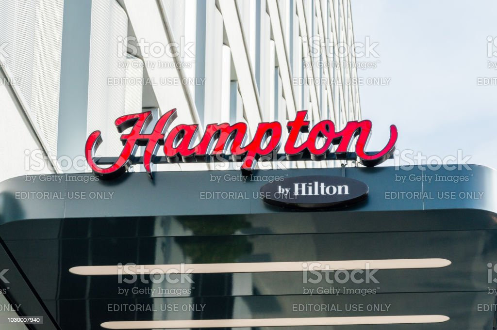 The Hampton by Hilton logo and sign. - foto stock