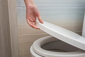istock The hand closes or opens the toilet lid 1135339546