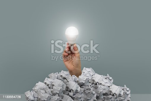istock The hand holding a light bulb emerges from the crumpled paper. 1133554726