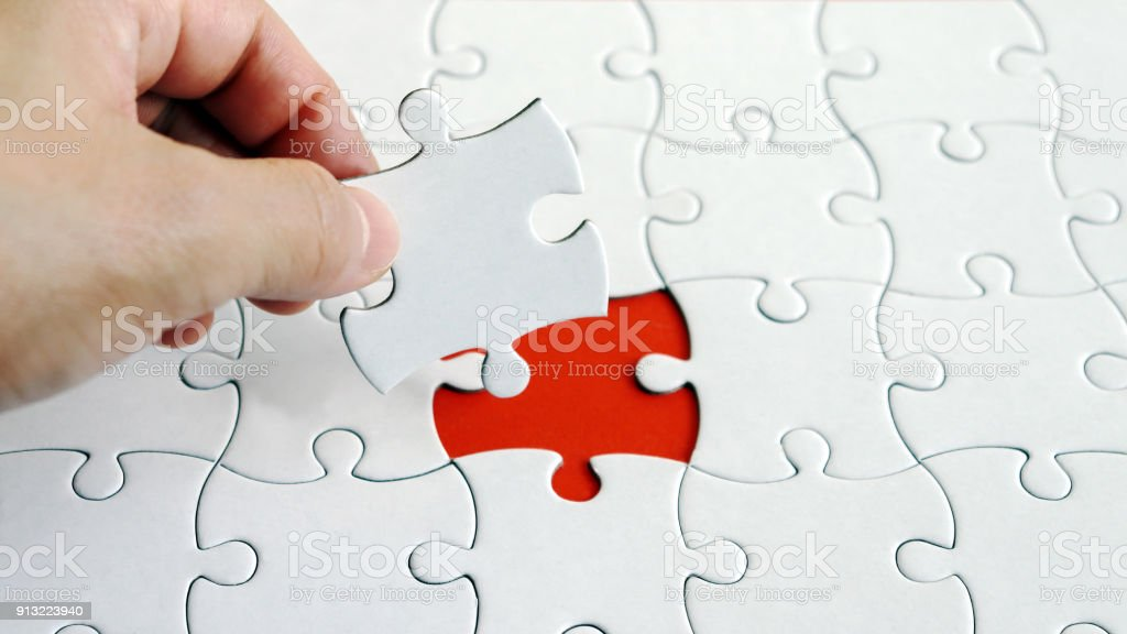 The hand holding a piece of the puzzle. A piece of a puzzle. stock photo
