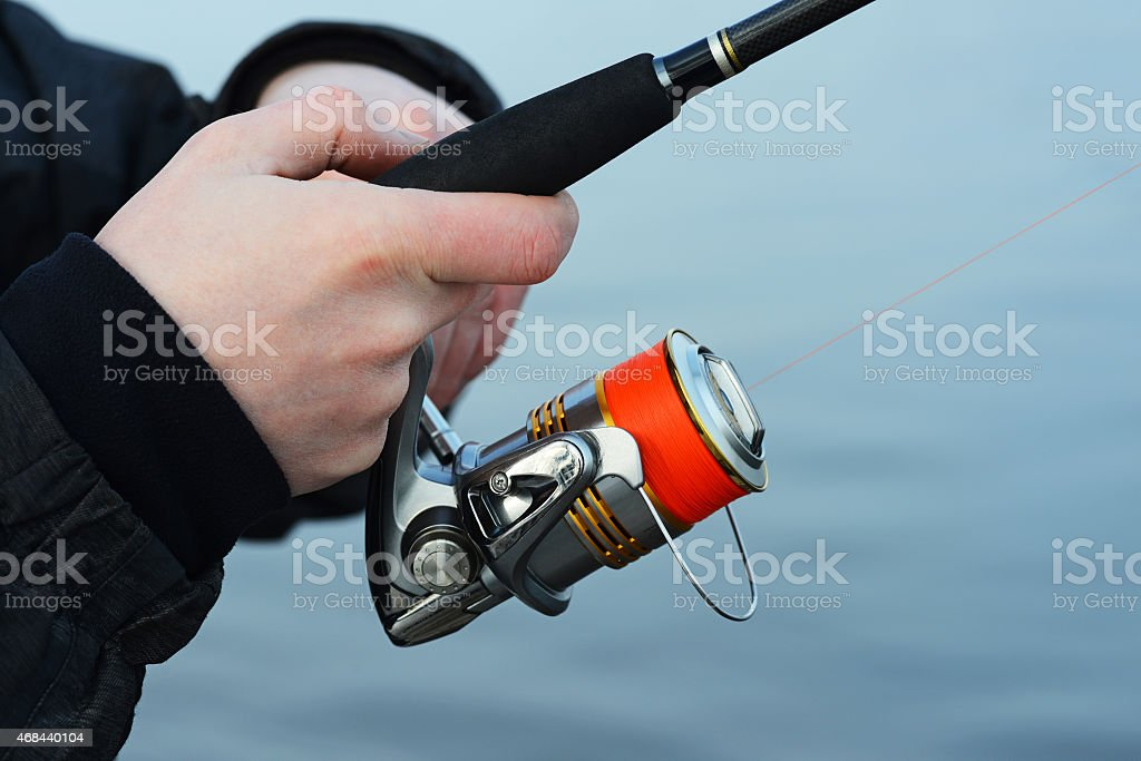 the hand holding the fishing rod stock photo