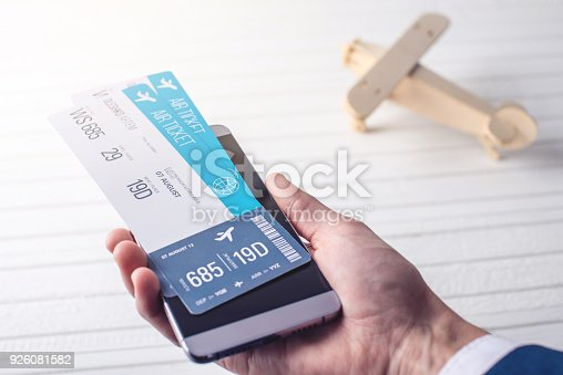 istock The hand holding the phone with the airline tickets. Concept of online purchase and booking of tickets for travel 926081582