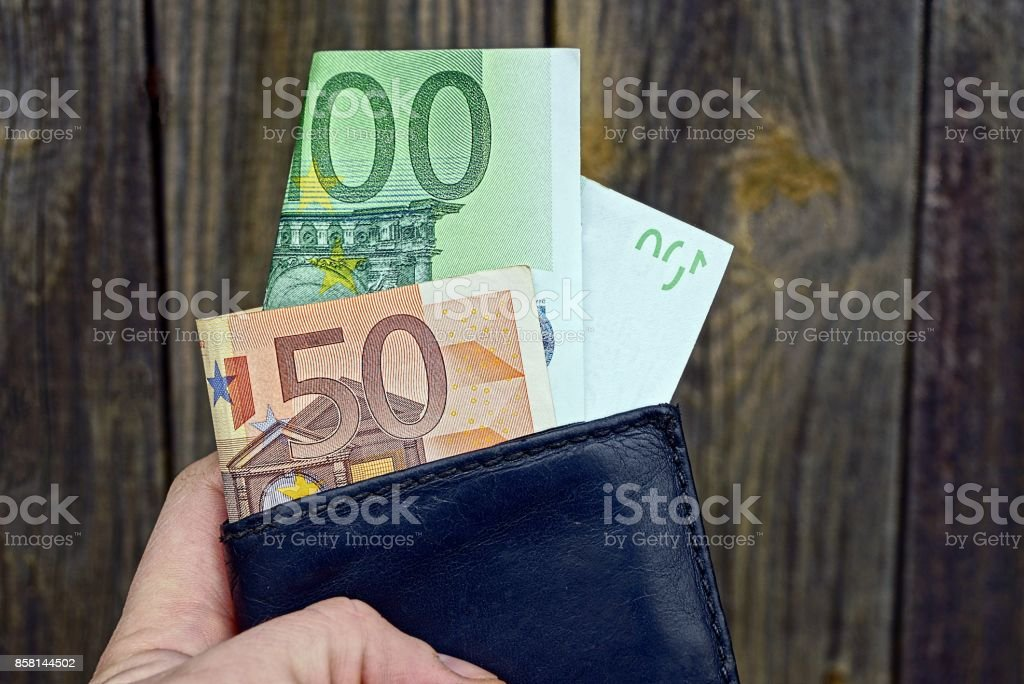 The hand holds a black leather wallet with cash notes stock photo