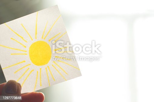 The hand holds a piece of paper with a drawn sun pointing at the sunlight in the room.