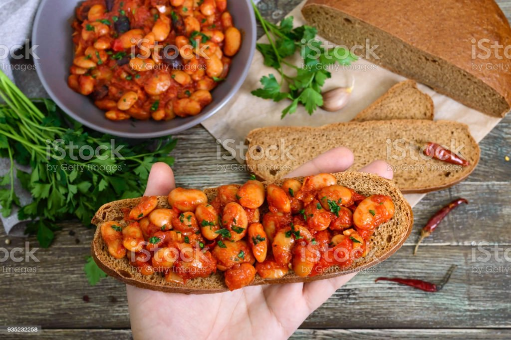 The hand holds a piece of rye bread with beans in the background of the table. Stewed beans in tomato sauce with herbs and spices. Top view. Lenten menu. Vegan dish. stock photo