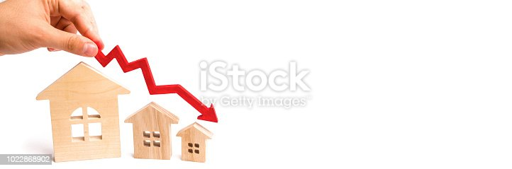istock The hand holds a red arrow above the wooden houses down. The houses are decreasing. The concept of falling demand and supply in the real estate market. Economic crisis. The fall in prices. 1022868902