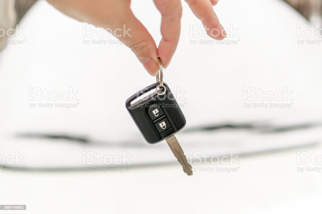 The hand holds the black key of the car. It's snowing. Winter. stock photo