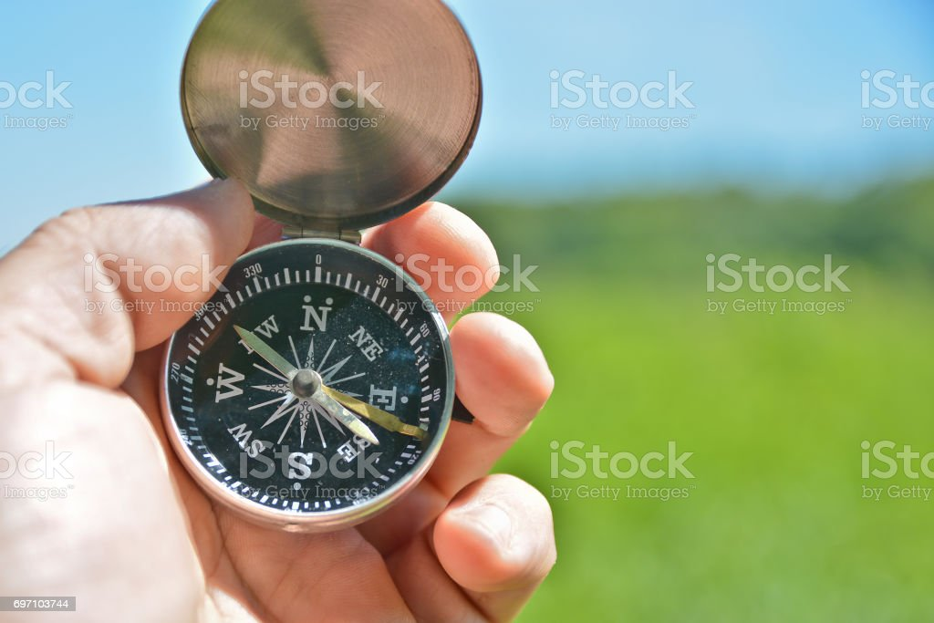 The hand holds the compass. stock photo